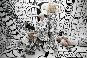 Members of Die Antwoord pose in front of black and white graffiti