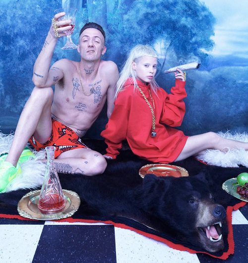 Member of Die Antwoord pose wth a bear skin rug, giant joint and glass.