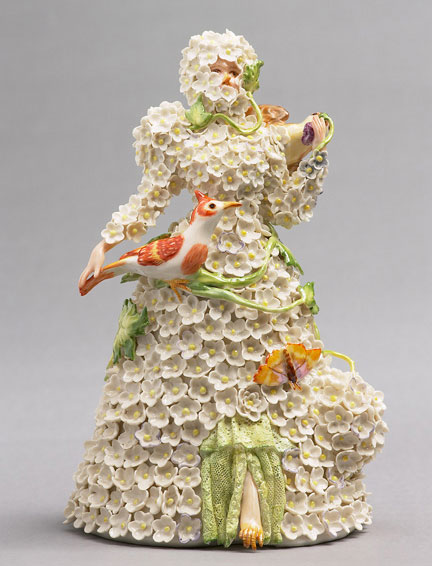 A porcelain figurine of a woman being choked by ornate flowers, by Shary Boyle.