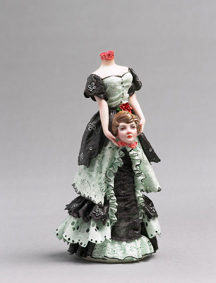 A porcelain figurine of a woman holding her own head, by Shary Boyle.