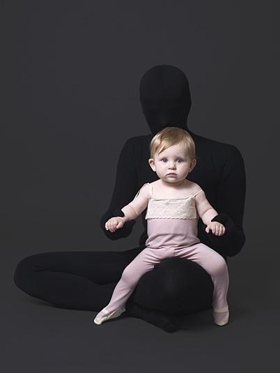 Baby girl models pink pyjamas with dark figure hidden in background.