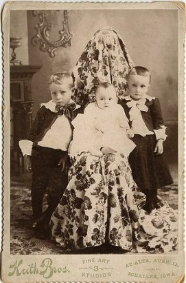 Three children pose in a Victorian photograph with a mother hiding in the background.