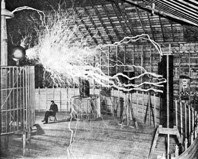 A picture of Nikola Tesla sitting in his lab demonstrating how safe his new AC electricity was, in 1899.