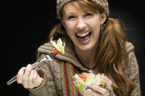Advertisement with woman laughing alone with salad.
