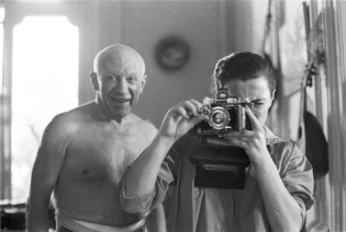 Pablo Picasso shirtless, taken in mirror.