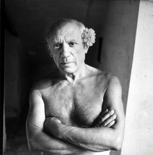 Pablo Picasso shirtless, with flower behind ear.