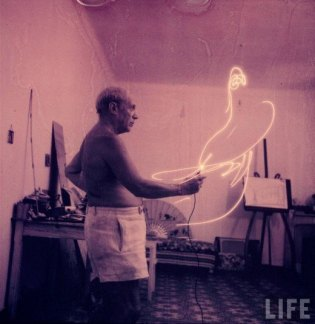 Pablo Picasso shirtless, painting with light.