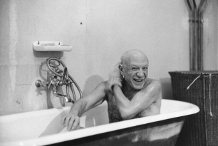 Pablo Picasso shirtless in bathtub.