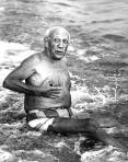 Funny photography of Pablo Picasso on the beach not wearing a shirt.