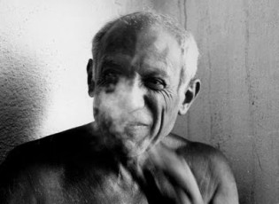 Pablo Picasso shirtless and smoking.