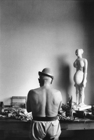 Pablo Picasso shirtless with bowler hat and drawing model.