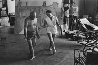 Pablo Picasso shirtless, dancing with woman.