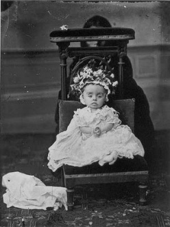 Post mortem photograph of child on chair with hidden mother behind.