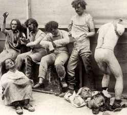 Photograph of six wax figures and broken body parts damaged from fire.