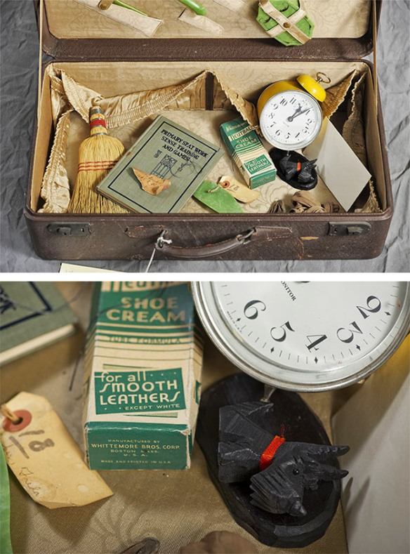 Abandoned suitcase with yellow alarm clock, straw broom, small Scotty dog figure, shoe polish cream and booklet.
