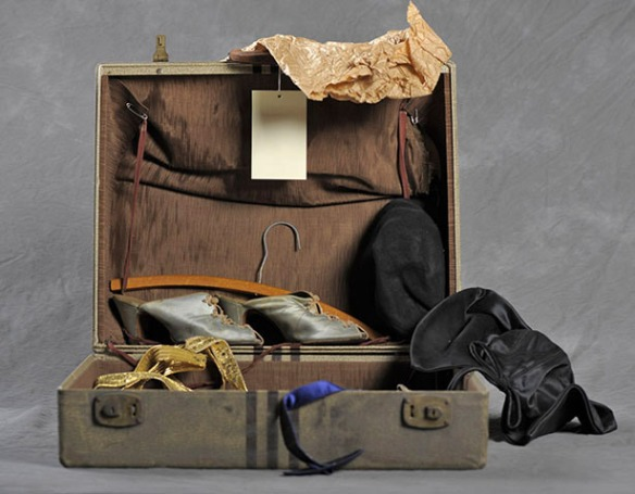 Open suitcase with black hat and blue shoes.