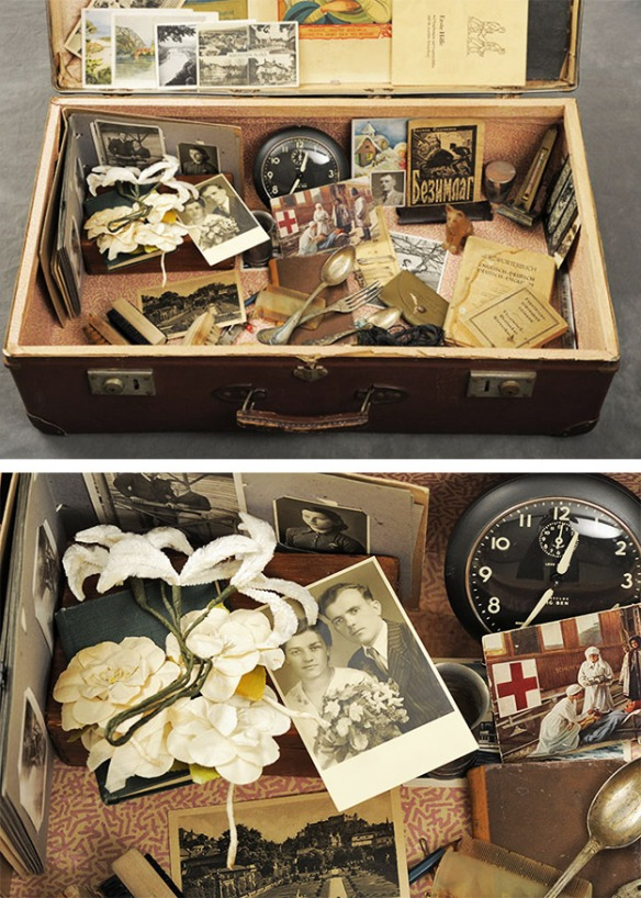 Open suitcase with vintage family photos, clock and fork and knife.