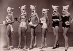 Contestants pose on beach with creepy bags placed over their heads.