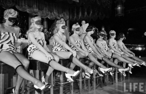 Contestants of beautiful legs contest wear masks and striped bathing suits, 1949.