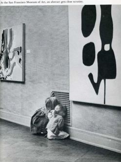 Two little girls captivated by looking through a vent instead of the modern art on the museum walls.
