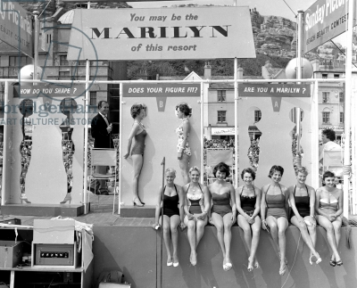 Contestants measure their bodies against cutouts of the star in a Marilyn Monroe look-a-like contest, 1958.