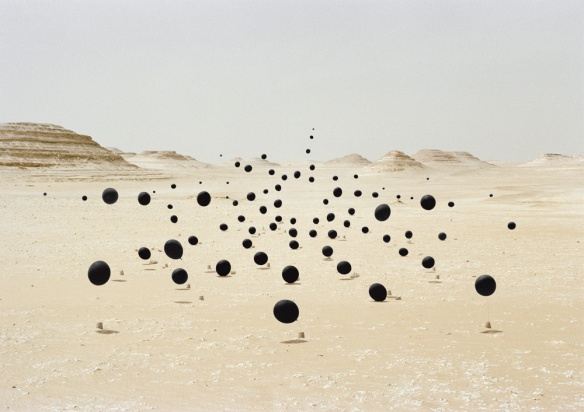 Surreal photo by Andrea Galvani of black balloons in desert landscape.