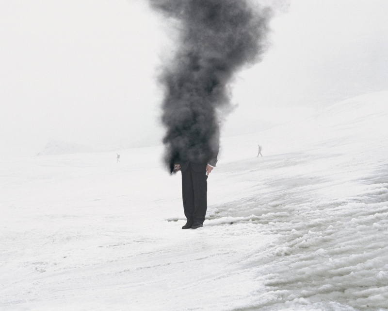 Photography by Andrea Galvani of a man standing in snow with upper half consumed by grey smoke.