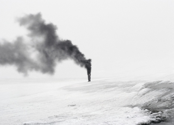 Surreal photo by Andrea Galvani of man consumed by grey smoke.