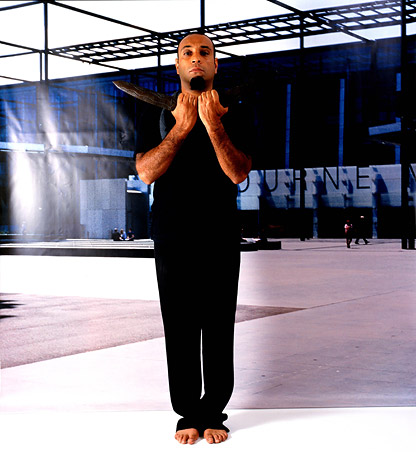 Image from Christian Thompson's Emotional Striptease (2003), (man in black with boomerang)