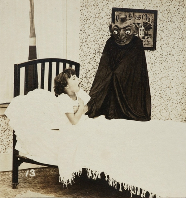 Image of a creature in a dark cape and devilish mask standing next to the bed of yawning little girl