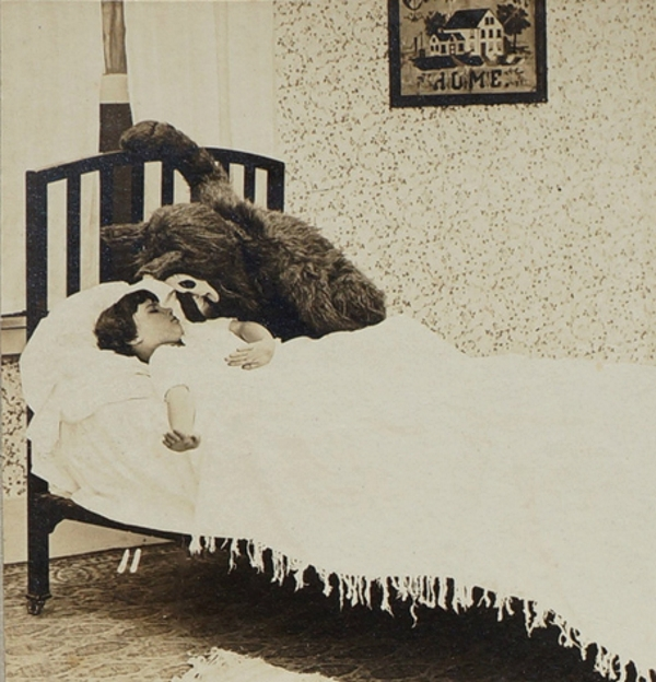 Image of a furry masked creature sitting on the bed of a sleeping girl