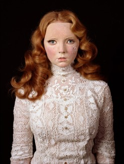 Photograph of model Lily Cole wearing a Victorian lace blouse and a damaged mask of her own face