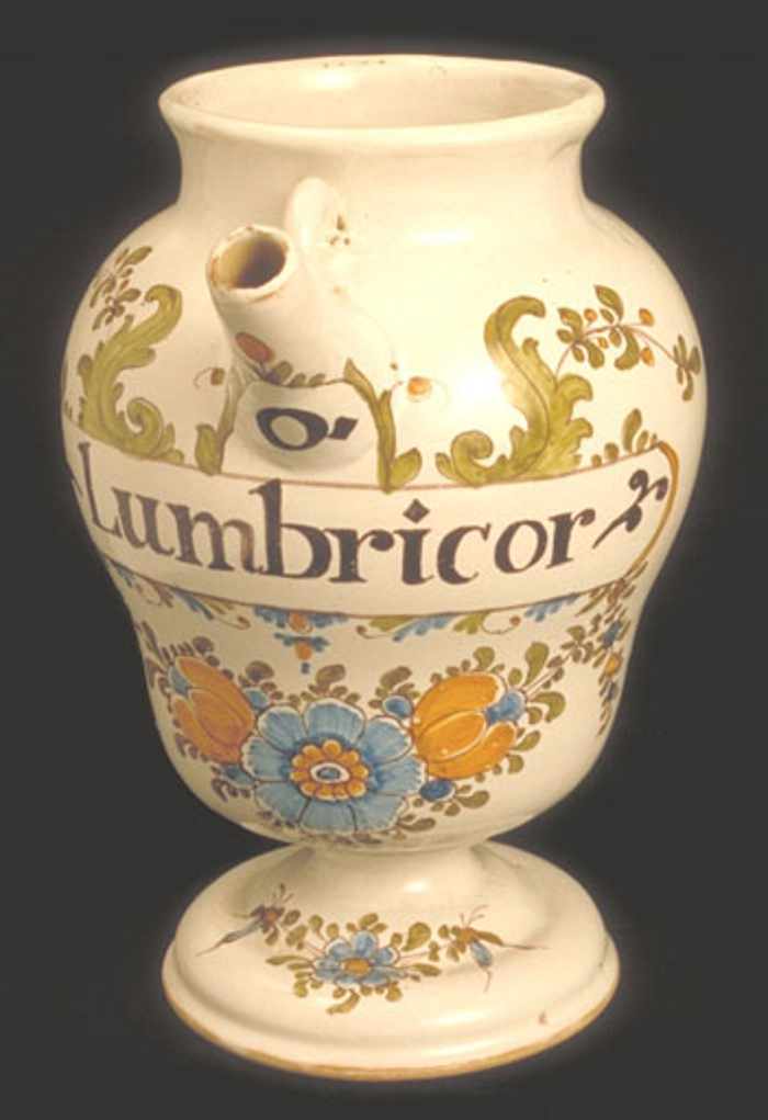 A photograph of an apothecary jar painted with the word 'Lumbricor' and floral decoration