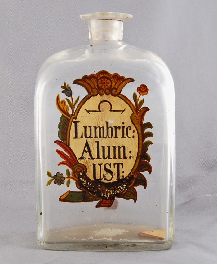 Clear glass apothecary bottle with painted label saying Lumbric: Alum: UST: and alchemical symbol for spirits