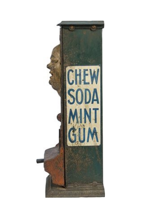 Side view of a vintage gum dispenser with creepy animatronic face and the words 'Chew Soda Mint Gum'