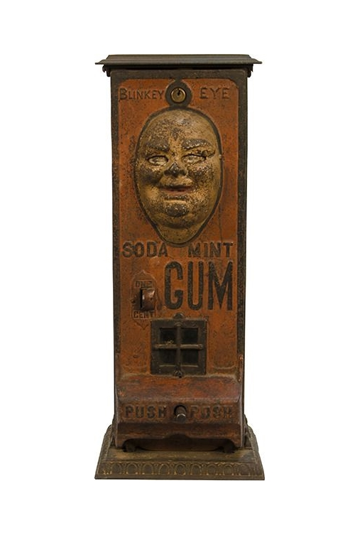 Vintage gum dispenser with a creepy animatronic face and the words 'Blinkey Eye Soda Mint Gum'