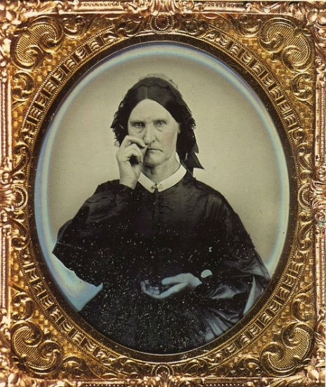 Photograph of a stern woman in black Victorian dress taking snuff, which looks very much like she is picking her nose.