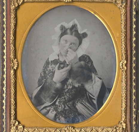 Photograph of a well-dressed Victorian lady taking snuff, which looks like she is picking fancy boogers out of her nose.