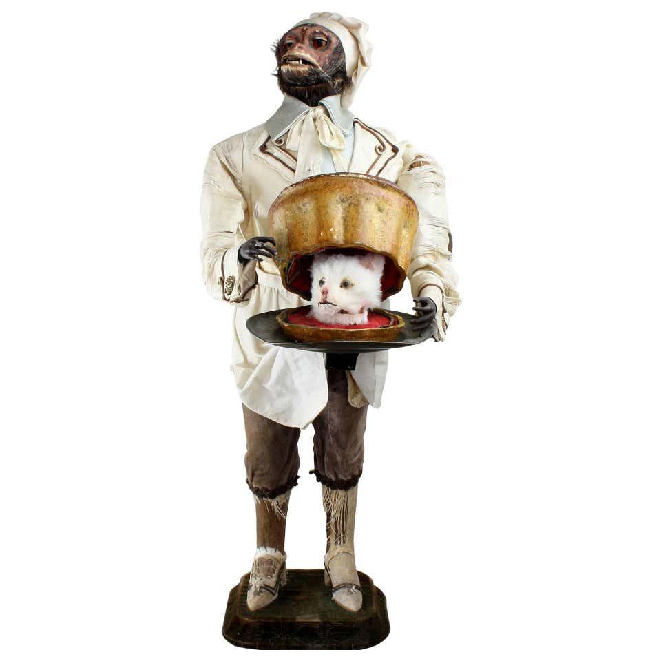Monkey automaton holding a pastry with the severed head of a cat inside